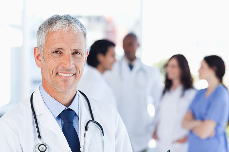 depositphotos 13909550-Mature-doctor-standing-upright-while-waiting-for-his-team